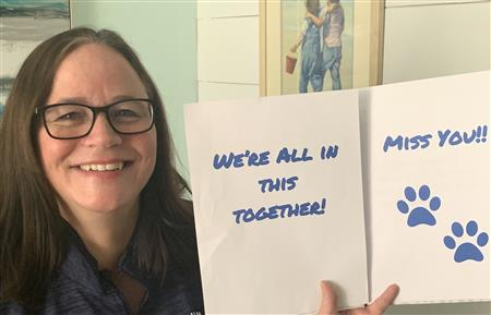 Teacher holding a we're all in this together miss you sign